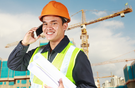 Portrait of an construction engineer holding blueprint convesation via phone with yellow crane and new building in the background