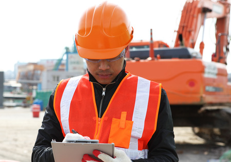 Builder engineer wearing safety work on construction location site writing on the board Stock Photo - 29861256