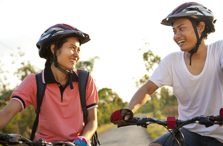 A young couple riding bicycles with helmets smile together