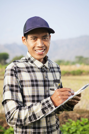 Farmer man smiling with notepad on hands Standard-Bild