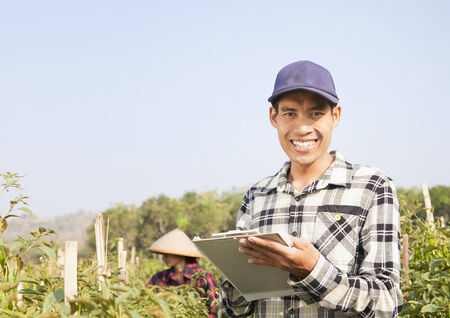 Happy farmers man holding notepad on chili peppers garden