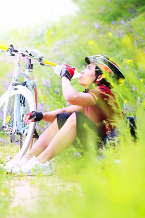 Cyclist resting and drinking, sitting on grass and flower