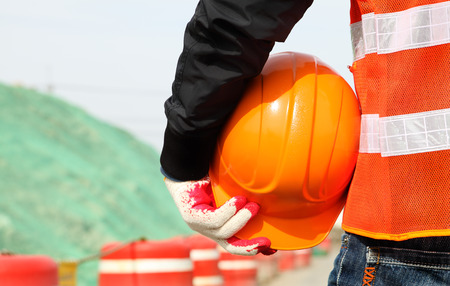 Close-up construction worker with safety vest holding hardhat on location site. Construction safety concept photo