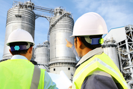 chemical plant: Two engineer oil gas refinery discussion under storage tank industry Stock Photo