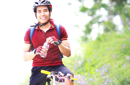 Happy man cyclist resting with holding water bottle