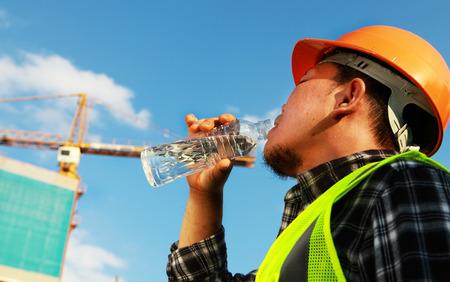 beber agua: Trabajador de construcción de agua potable en un sitio de ubicación Foto de archivo