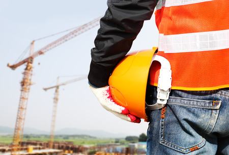 Construction safety concept, close-up worker holding hardhat with crane in the background photo