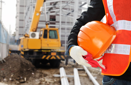 work safety: Construction safety concept, close-up worker wearing safety vest holding helmet with crane in the background