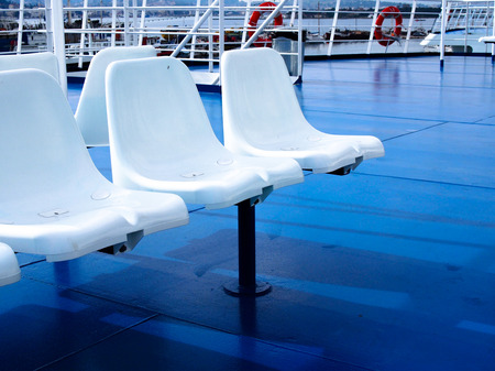 ferry boat: Wite Plasic chairs on Blue colour Ferry boat. Stock Photo