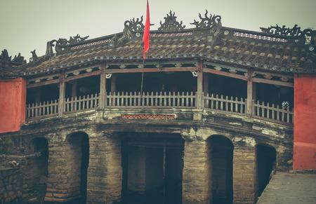 View of the Japanese Covered Bridge (Cau Chua Pagoda, Cau Nhat Ban, Lai Vien Kieu), Hoi An Ancient Town (Hoian), Vietnam. Blue sky in background. The old bridge is a popular tourist attraction of Asia