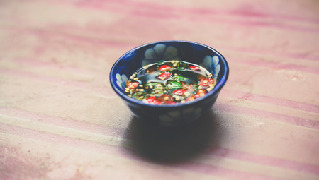 Nuoc Mam - Vietnamese Spicy Fish Sauce in Small bowl on Wooden Background Stok Fotoğraf