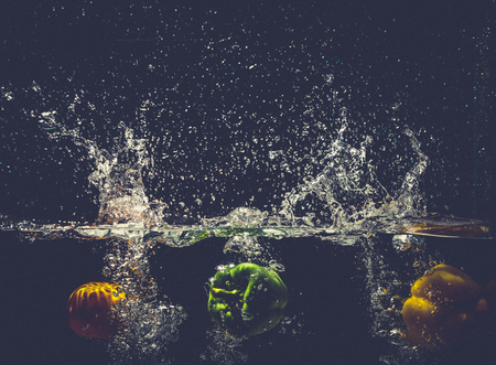 Green yellow bell peppers drop into the water with splash.