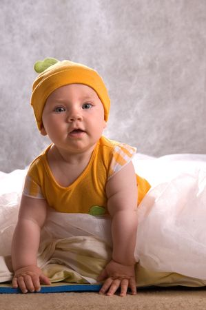 Cute Baby with an Orange Hat Climbing out of Bed photo