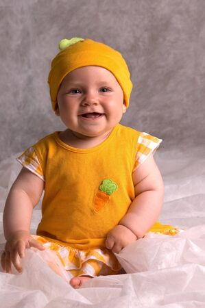 expressing: Cute Smiling Baby with an Orange Hat