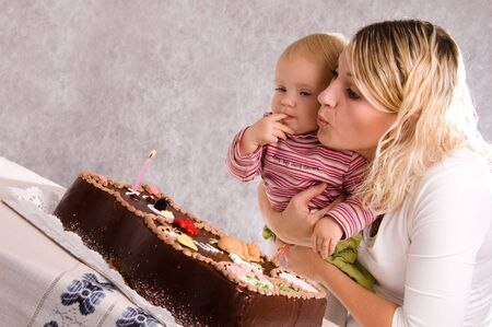 baby girls smiley face: Mum and her baby daughter leaning over a birthday cake