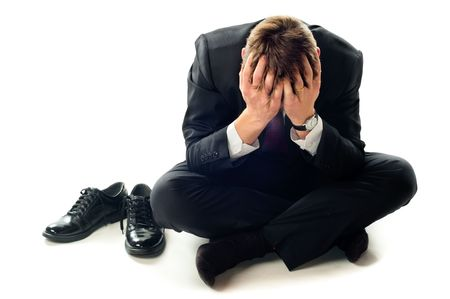 distraught: Depressed businessman sitting on the floor. Isolated on white background.