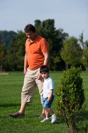 Grandpa and his grandson are walking in the park   photo