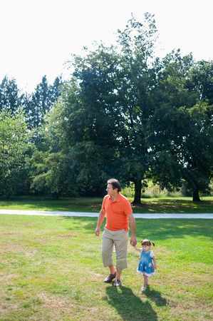 Grandfather and his granddaughter walking in the park photo