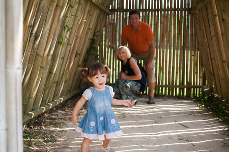 Family having fun in a little house made of bamboo photo