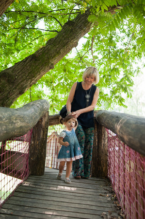 Mother and her daughter are walking on the wooden bridge photo