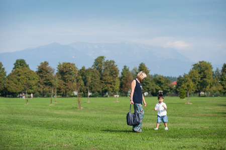 walk in: Mother and her son are having fun in the park