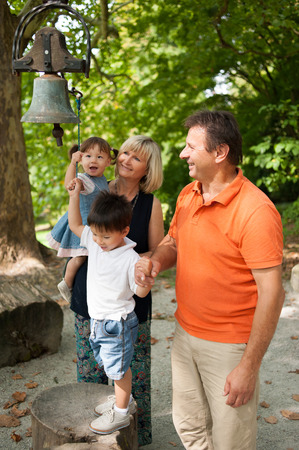 Family and the bell in a park photo