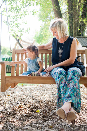 2 50: Woman and little girl are sitting on the bench and having a great time