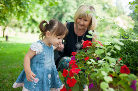 Woman and little girl admiring red flowers photo