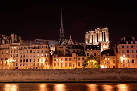Paris by night: ile de la cit� with side view of Notre Dame cathedral as seen from river Seine bank photo
