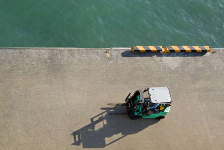 manoeuvre: Aerial view of a fork lift manoeuvring in the dock