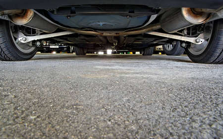 An unusual view of a car parking, from below a car.