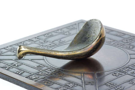 reproduction: Reproduction of an ancient Chinese compass (which points south) on white background