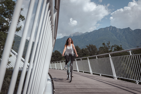 Young attractive woman with bicycle on a bridge surrounded by nature and architecture during a cloudy day Reklamní fotografie