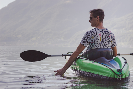 young adult with a green kayak in the lake of Locarno in the morning 写真素材