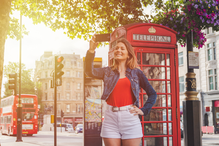sidewalk in the street of england. woman dressed with casual clothing. Phone Booth and double decker bus as background