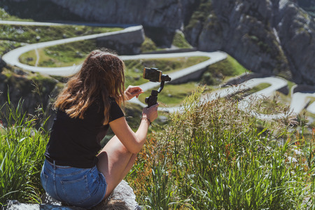 girl using an image stabilizer with his phone in the swiss alps Imagens