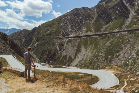 tremola road in san gottardo during a sunny day with a boy and his skateboard