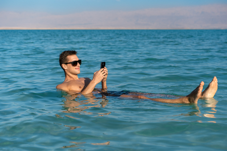 man taking a tan and relaxing in the dead sea. Checking social media with the phone