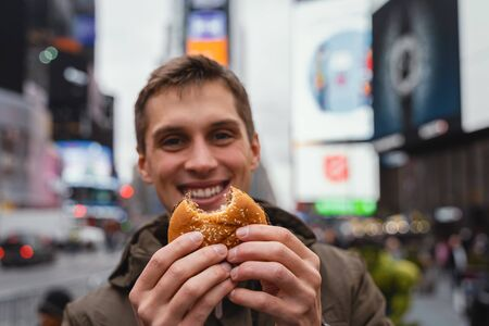 Male eat hamburger in the streets of new york