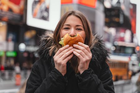 female eat hamburger in the streets of new york