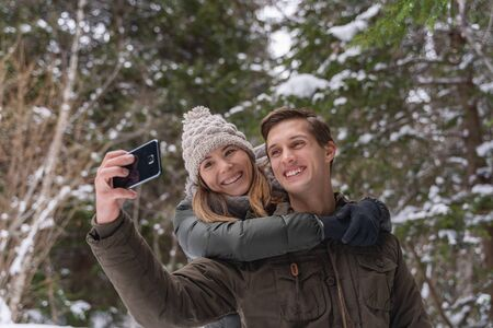 couple in love enjoying the winter season before christmas walking in the snowy forest Stock fotó