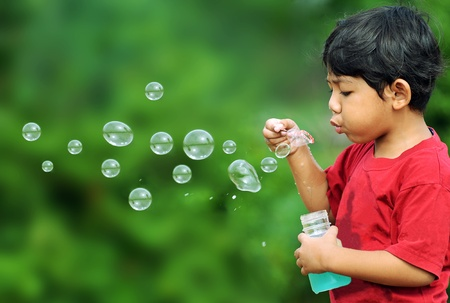 blowing bubbles: Cute young boy playing with bubbles Stock Photo