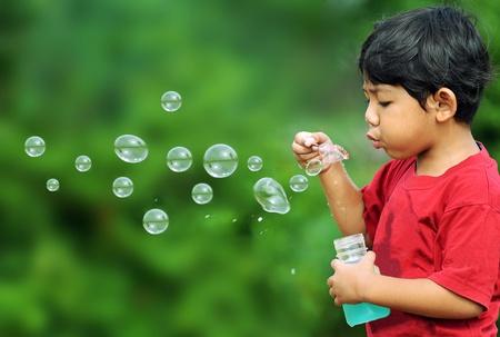 niños jugando en el parque: Niño lindo jugar con burbujas Foto de archivo
