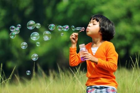 burbujas de jabon: Niños jugando con pompas de jabón sobre un fondo verde entorno