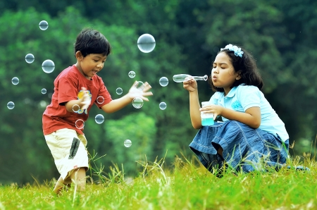 Children playing with soap bubbles on a green environment background