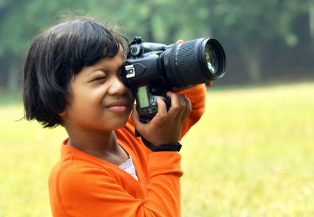 slr camera: Young asian girl taking picture with Digital SLR camera Stock Photo