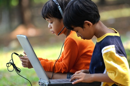 Young children, boy and girl using laptop and listening to digital music in outdoor scene photo
