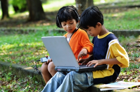 use computer: Young children, boy and girl using laptop and listening to digital music in outdoor scene
