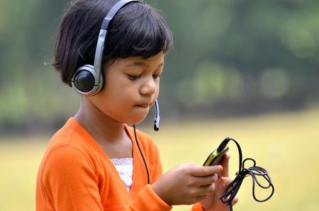 Cute asian giovane, l'ascolto di musica digitale da uno smartphone con un auricolare