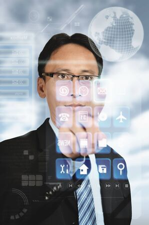 An asian businessman accesing the digital information on hitech holographic screen Imagens